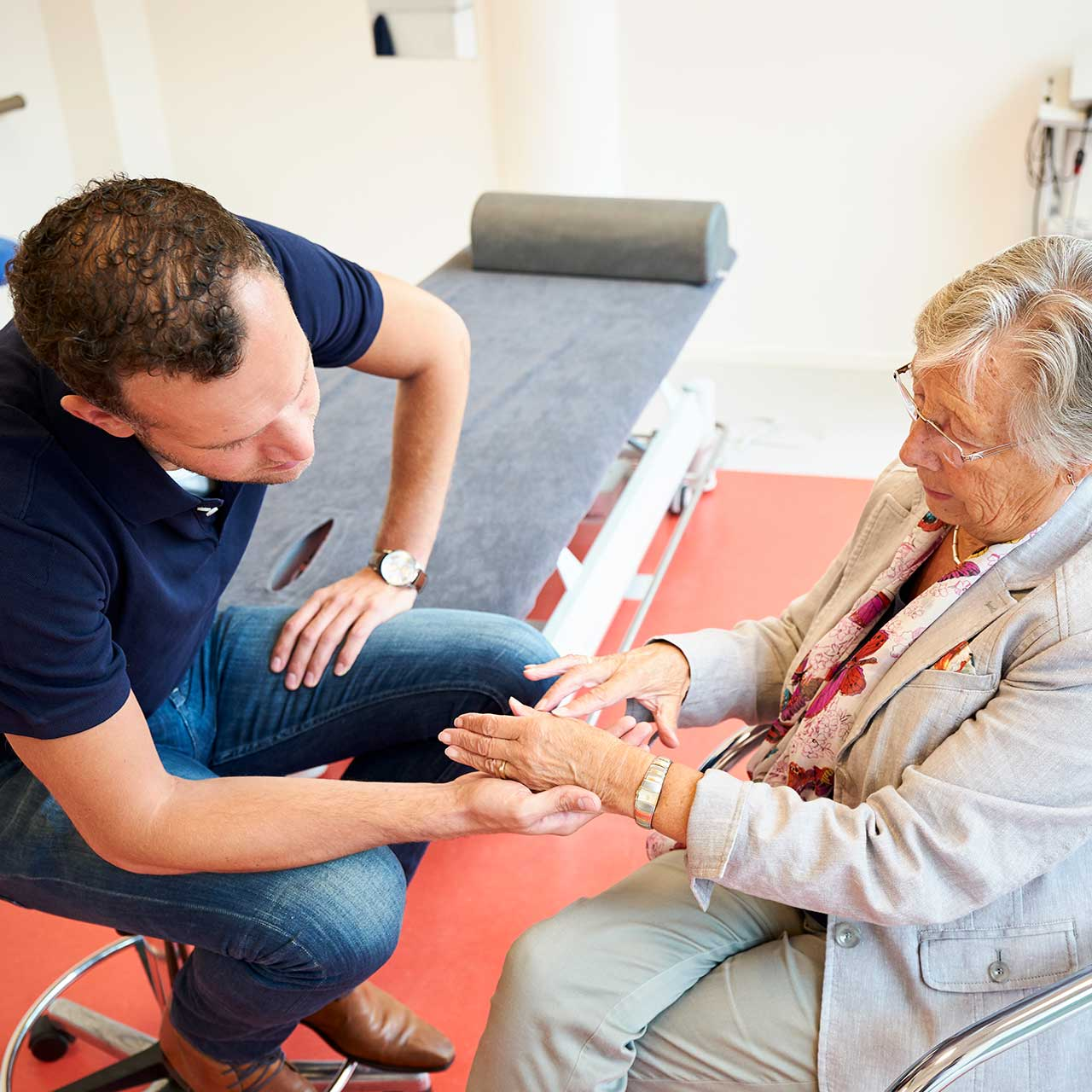 Oudere vrouw laat zien waar klachten zitten aan therapeut | Fysio Stenia Zeist