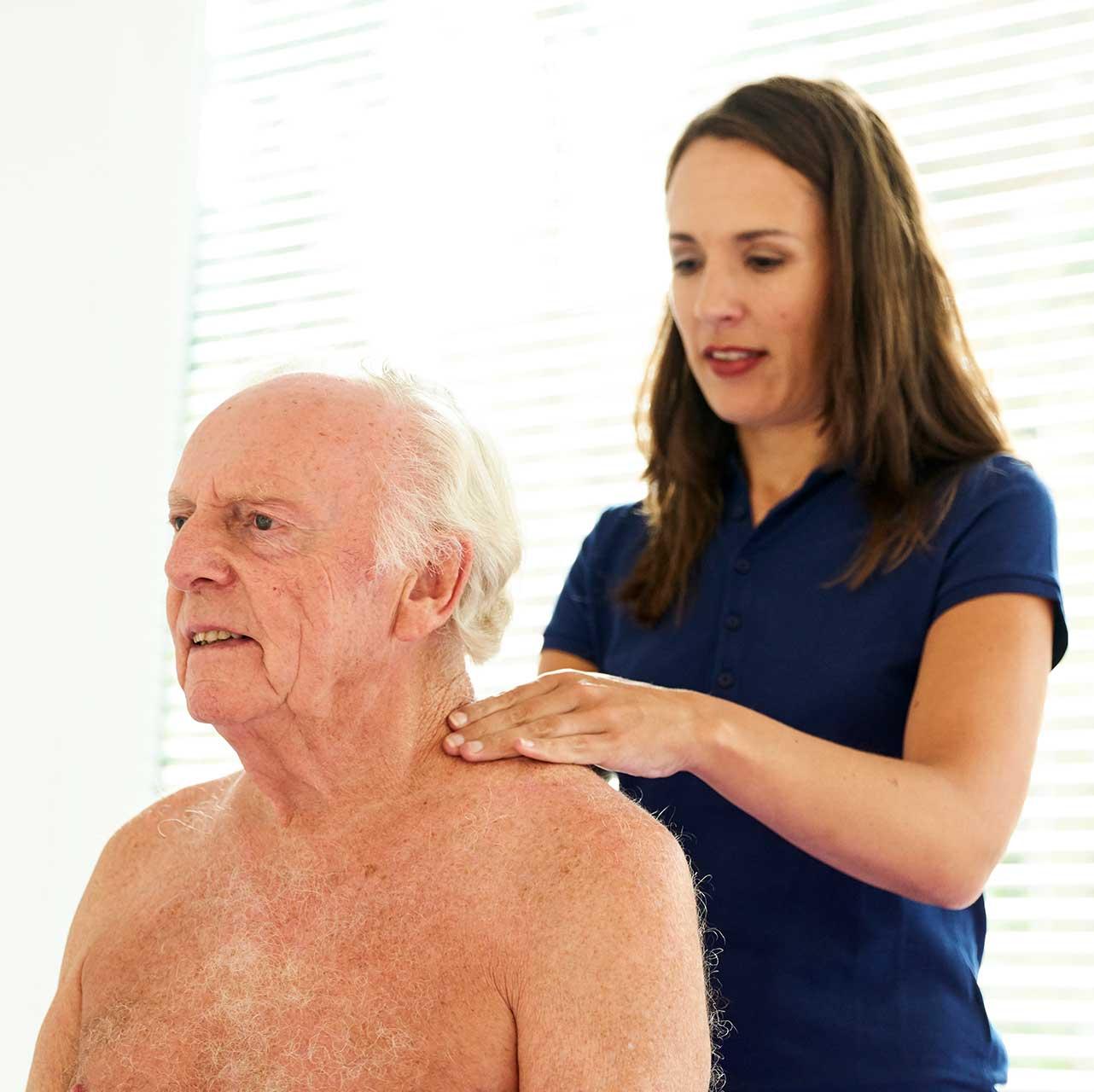 Behandeling van schouders oudere man door vrouwelijke fysiotherapeute | Fysio Stenia Zeist