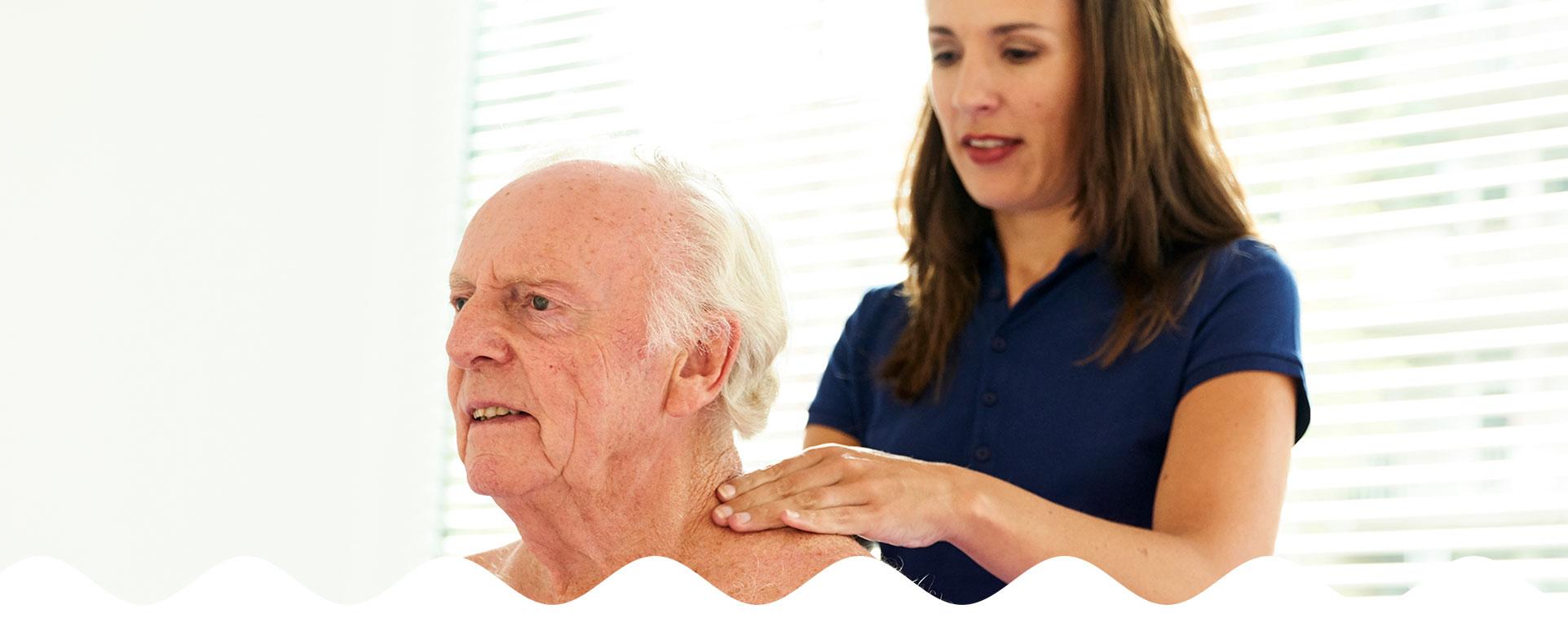 Oudere man wordt behandeld aan schouder door vrouwelijke fysiotherapeute | Fysio Stenia Zeist