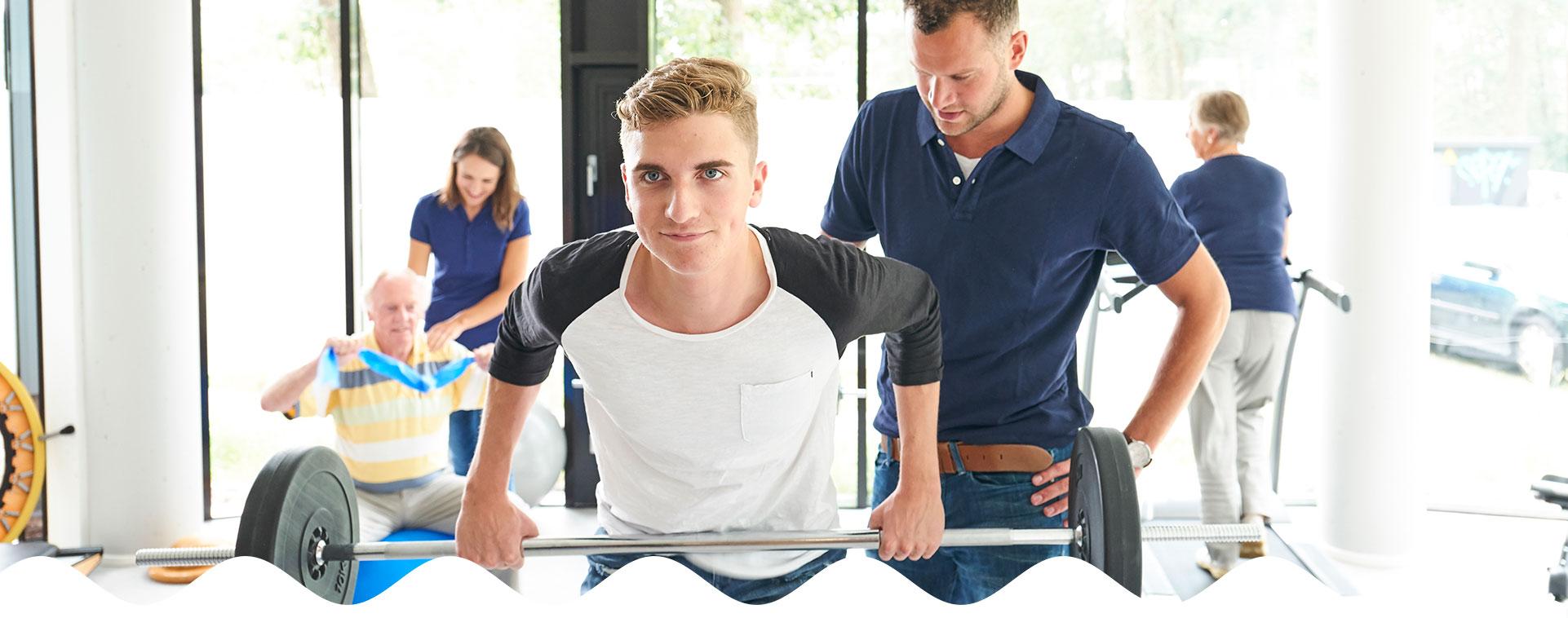 Jongen met gewichten tijdens sporten in zaal | Fysio Stenia Zeist