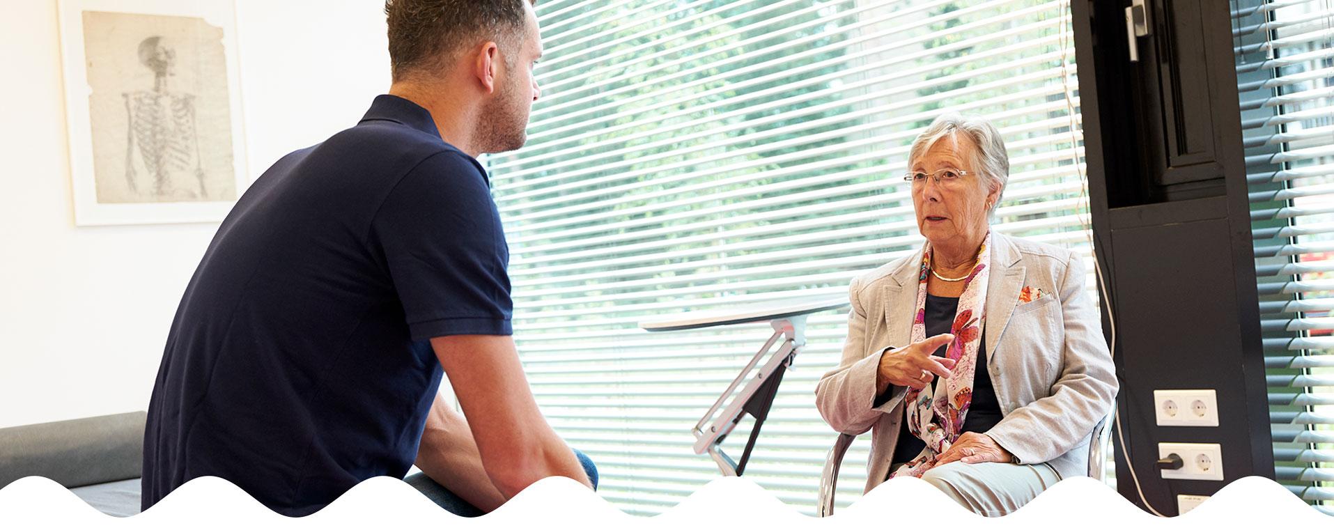 Oudere vrouw in gesprek met mannelijke fysiotherapeut | Fysio Stenia Zeist