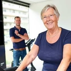 Oudere vrouw op de hometrainer onder toezicht van fysiotherapeut | Fysio Stenia Zeist